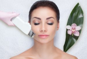 the ultrasound cleaning procedure of the facial skin of a beautiful woman in a salon.